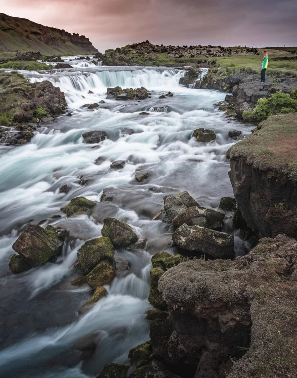 girl standing next to waterfall in Iceland during a sunset